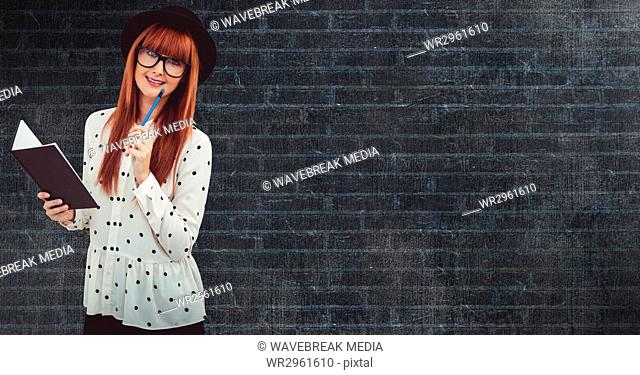 Female hipster holding book against wall