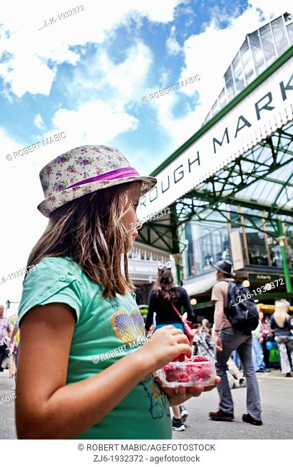 Girl eating raspberries at the Borough Market in London
