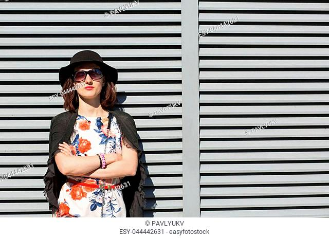Lovely brunette woman wearing stylish dress and sunglasses, posing near the shutters at the street. Space for text