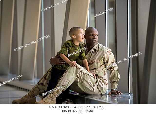 African American soldier and son looking out airport window