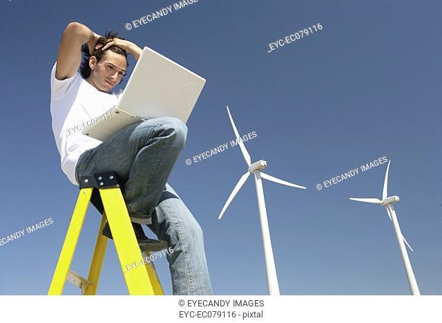 Young man sitting on ladder using laptop near wind farm