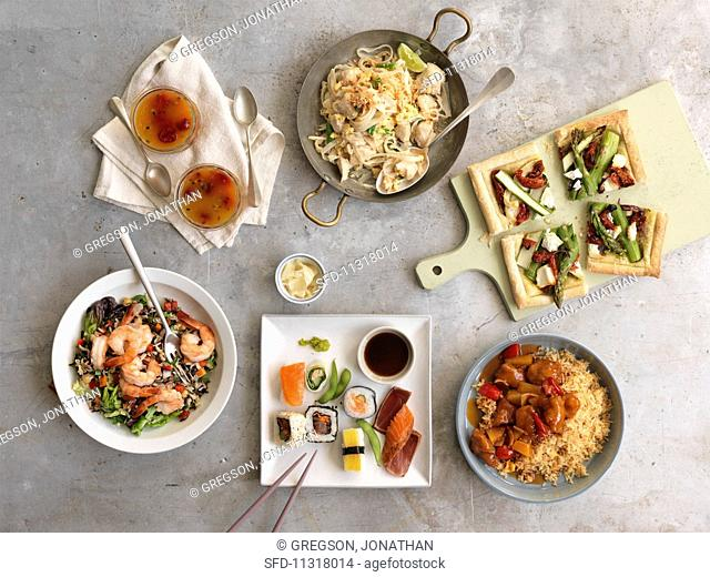 A buffet with sushi, vegetable tart, noodles, sweet and sour chicken, prawn salad and passion fruit jelly