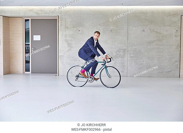 Businesssman riding bicycle in office building