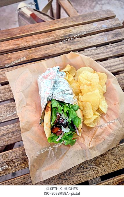 Meal of salad wrap and potato chips