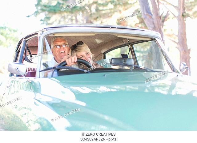 Senior man and mature woman in car together, smiling