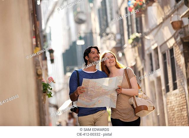 Smiling couple with map on narrow street in Venice