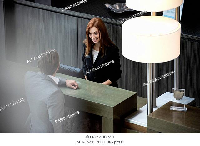 Female receptionist talking with businessman