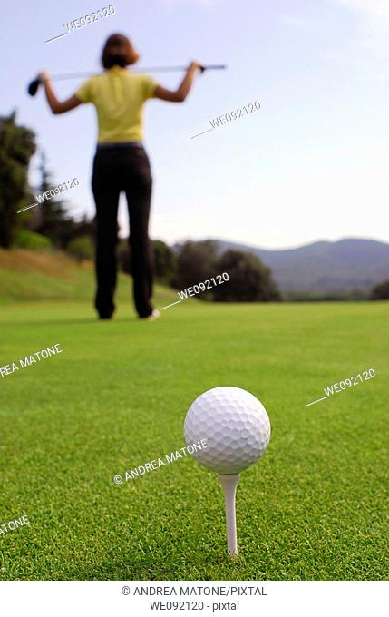 Young woman golfer observing terrain and conditions before hitting