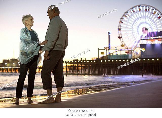 Senior couple on beach at night