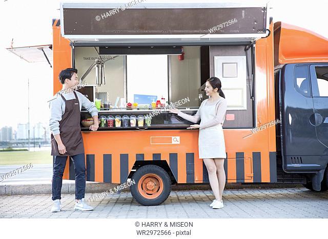 Young smiling vendors posing at food truck