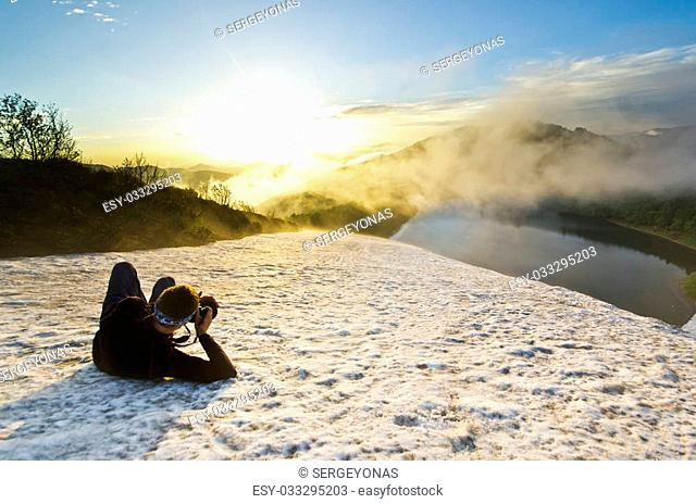 man with camera making photo on a snow hill at sunset and clouded sky