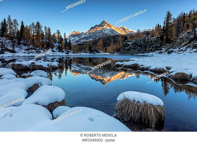 The rocky peak reflected in the frozen Lake Mufule at dawn, Malenco Valley, Province of Sondrio, Valtellina, Lombardy, Italy, Europe
