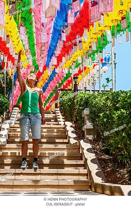 Female tourist pointing at rows of lanterns honoring buddha birthday in Naksansa Temple, Naksansa, Yangyang, Gangwon province, South Korea