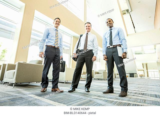 Low angle view of businessmen smiling in office lobby