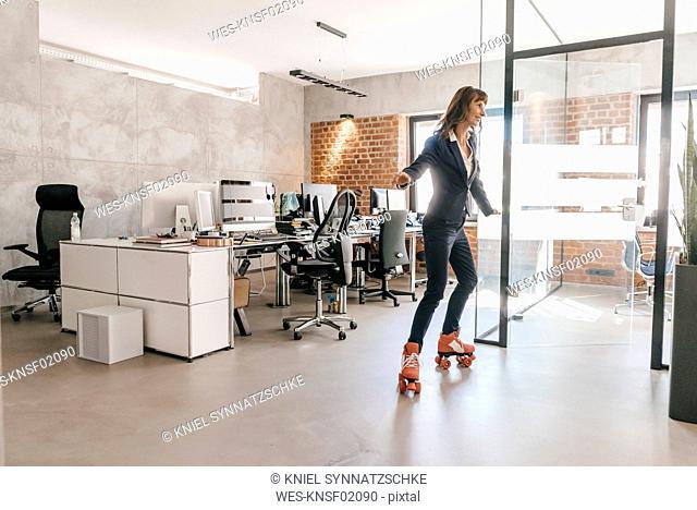 Successful businesswoman wearing roller skates in office