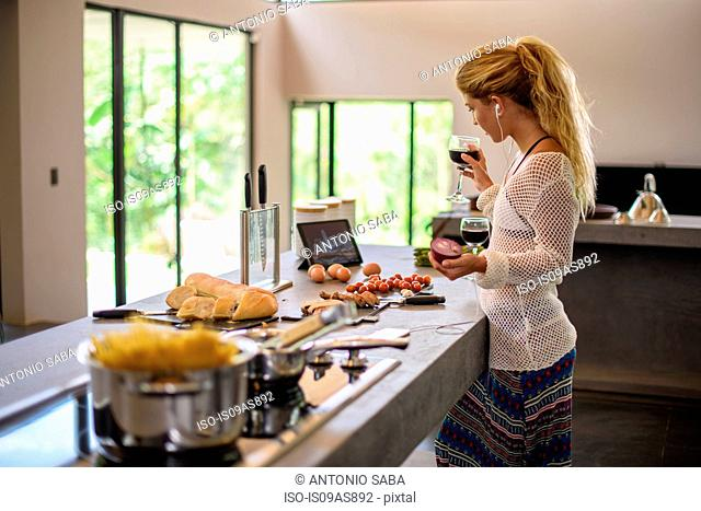Young woman multi tasking whilst preparing food in kitchen