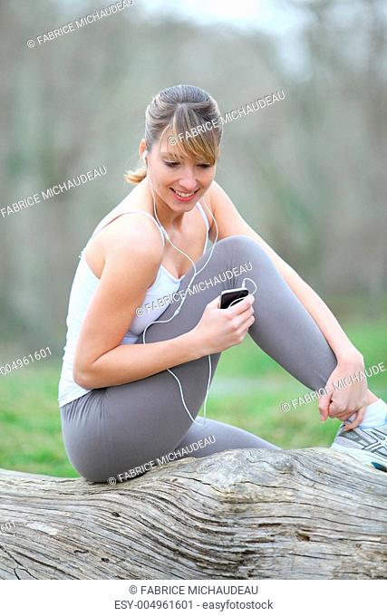 Woman jogging in forest with music player