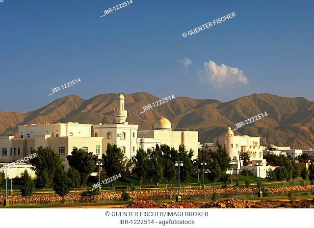 New housing estate with mosque and minaret, in front of stark mountains, Muscat, Sultanate of Oman, Middle East
