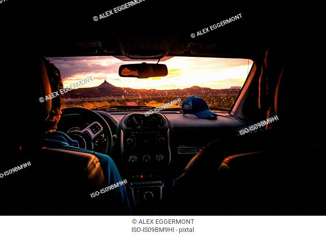 Driver and friend in car watching sunset, Indian Creek, Moab, Utah, USA