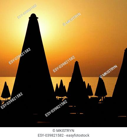 silhouettes of many furled beach umbrellas on the beach on sunset time, Italy,Europe