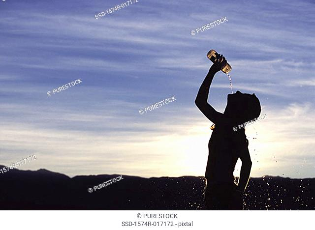 Silhouette of a man drinking water at dusk
