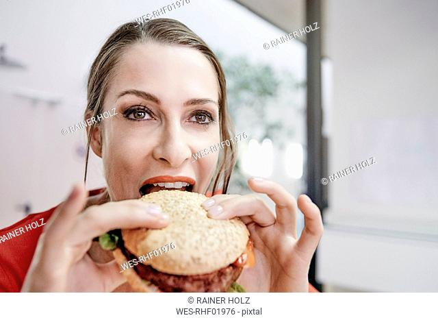 Woman eating a vegan hamburger