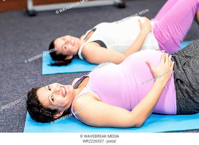 Pregnant women lying on exercise mat