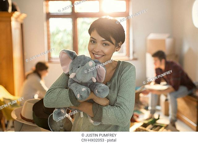 Portrait smiling young woman holding stuffed elephant