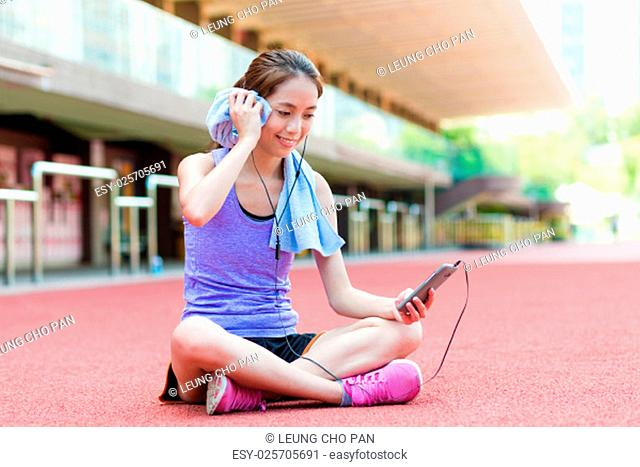 Woman look at the phone after doing exercise