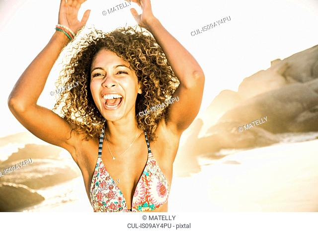 Happy woman raising arms on beach