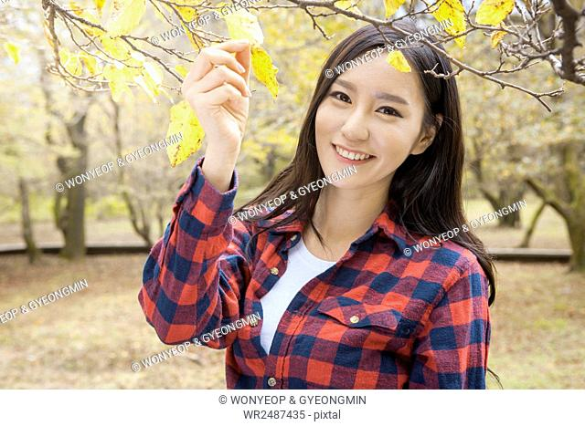 Portrait of young smiling woman touching autumn leaves