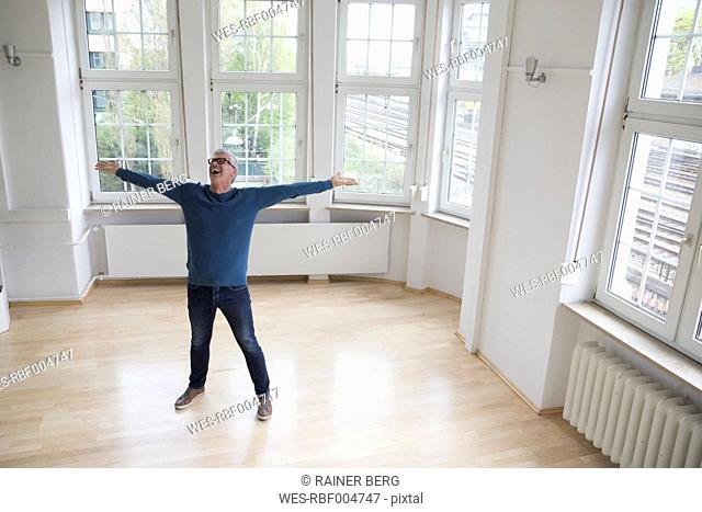 Happy man standing in empty apartment
