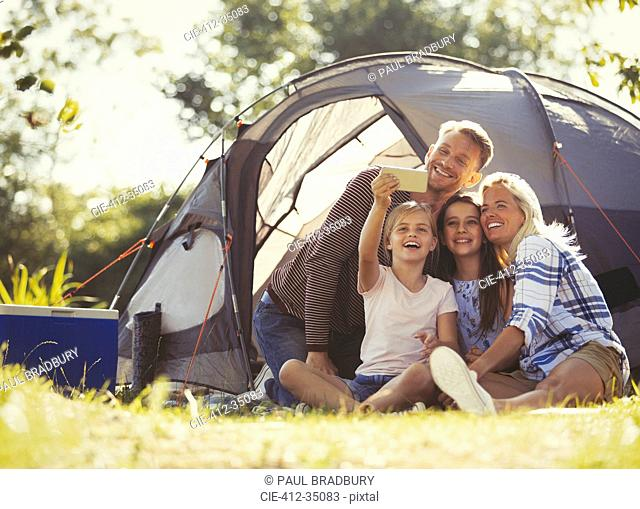 Family taking selfie with camera phone outside tent at sunny campsite