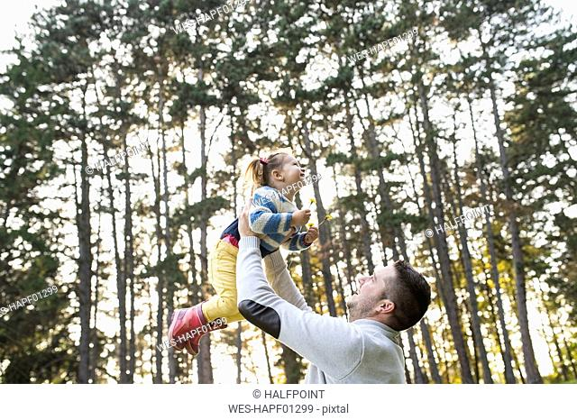 Father lifting up his daughter in forest