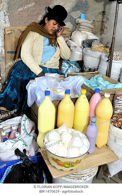Street sale of fresh cheese and other agricultural products from the Penas Valley, saleswoman on a mobile phone, Oruro, Bolivia, South America