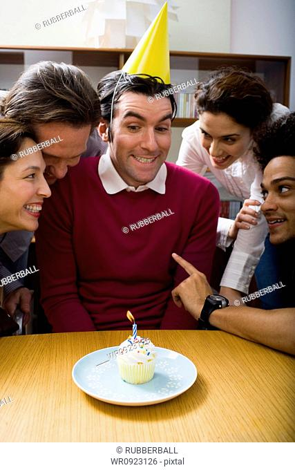 Co-workers around a birthday cupcake