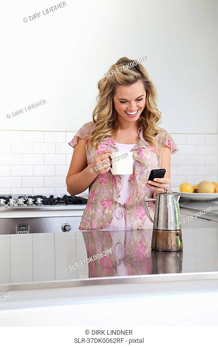 Woman using cell phone in kitchen