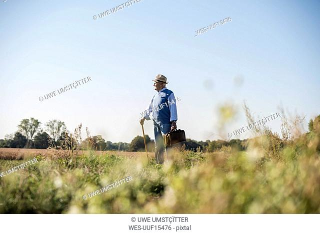 Senior man carrying traveling bag, walking in the fields