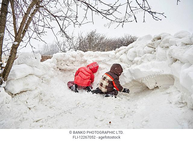 Kids building a snow fort; Ontario, Canada