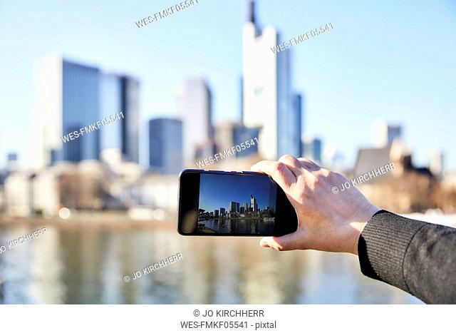 Germany, Frankfurt, hand taking photo of financial district with cell phone