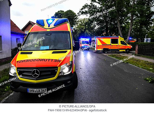 12 June 2019, Germany (German), Oranienburg: After a thunderstorm, rescue vehicles are standing in front of a building where several people were injured by the...