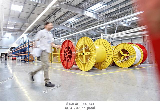 Male worker walking by large spools in fiber optics factory