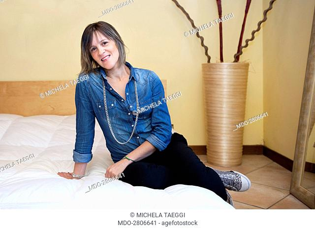 A woman posing seated on a bed. Caprino Bergamasco (Italy), 15th October 2014