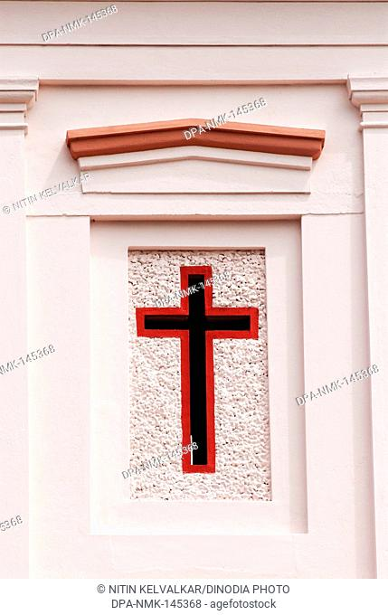 The simple Crucifix ; the oldest symbol of Christianity colourfully painted on wall of church ; Madurai ; Tamil Nadu ; India