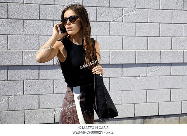 Fashionable young woman in front of brick wall on the phone