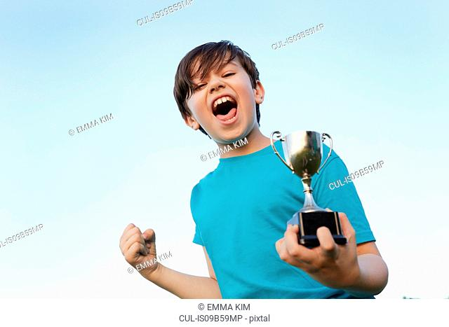 Boy making fist and holding sport trophy against blue sky