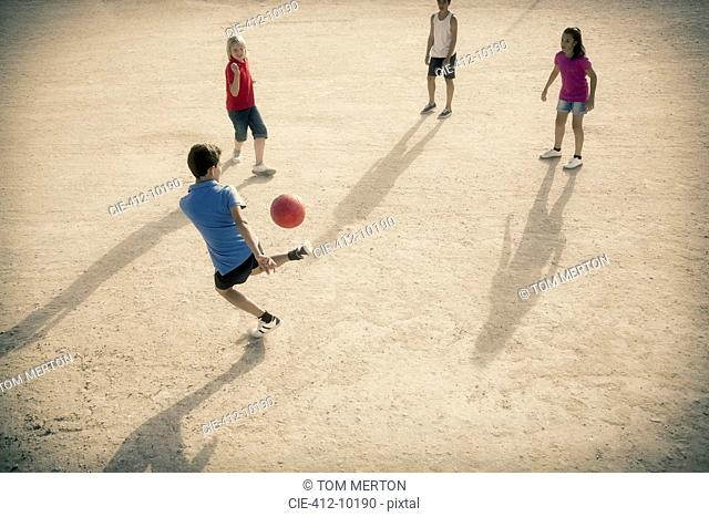 Children playing with soccer ball in sand