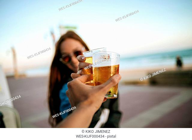 Clinking beer glasses by the sea