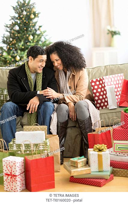 Couple with Christmas presents in living room