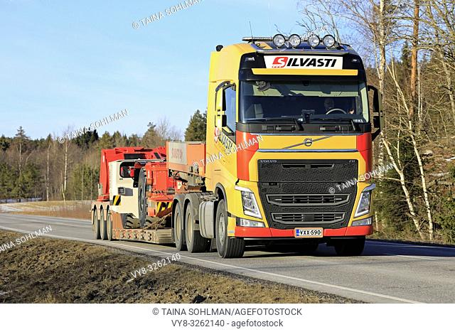 Salo, Finland - March 1, 2019: Yellow Volvo FH truck of Silvasti hauls Sandvik LH209L underground loader or LHD on trailer on highway on day of spring